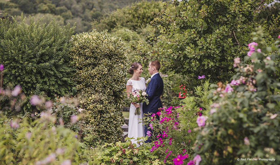 Newlyweds explore the gardens at Upwaltham Barns on their wedding day