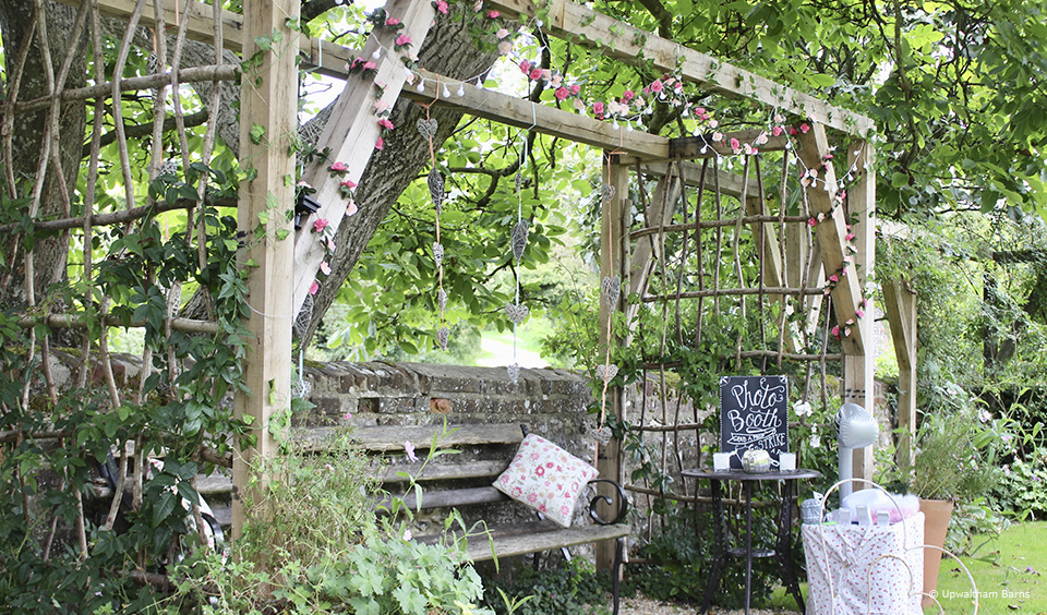 A couple created an outdoor wedding photobooth in the gardens at Upwaltham Barns for their wedding reception