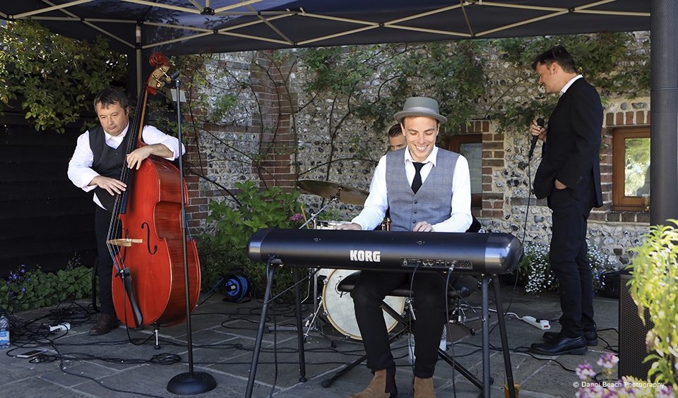 A wedding band entertain guests during a drinks reception at Upwaltham Barns