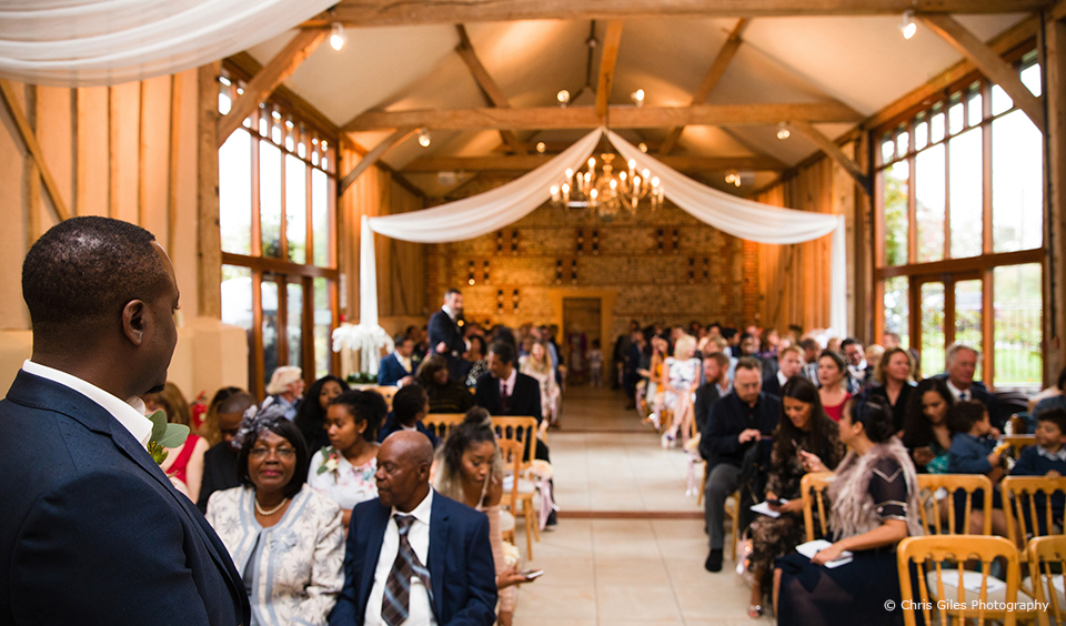 Wedding guests await the bride for a wedding ceremony in the East Barn at Upwaltham Barns