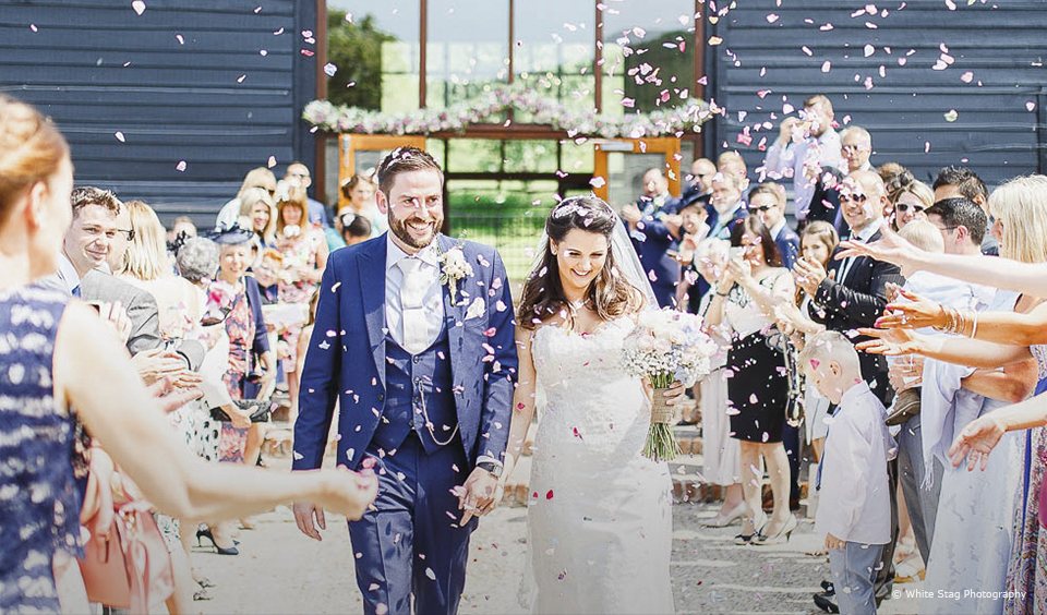 Newylweds are showered in wedding confetti after their wedding ceremony at Upwaltham Barns