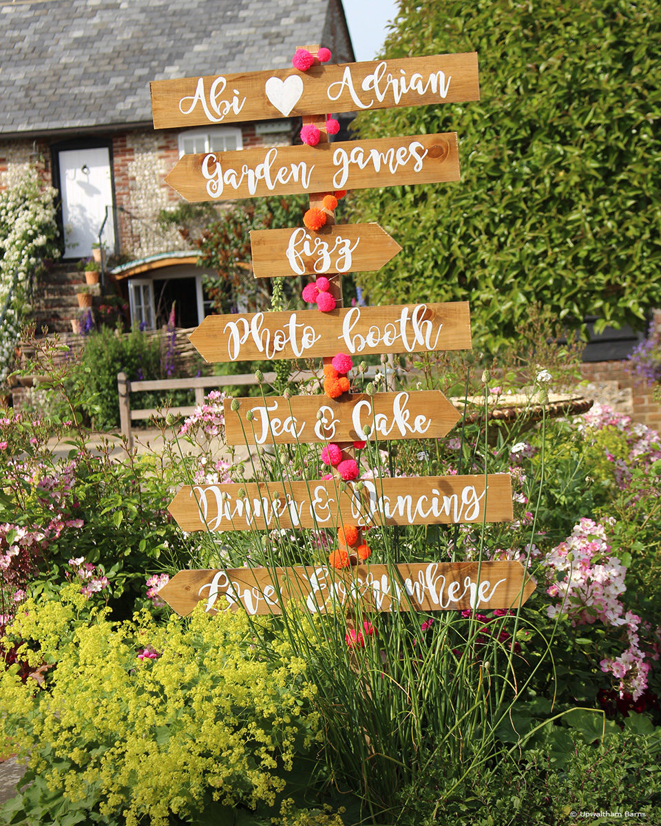 A wedding sign sits in the courtyard at Upwaltham Barns to direct guests around this Sussex wedding venue