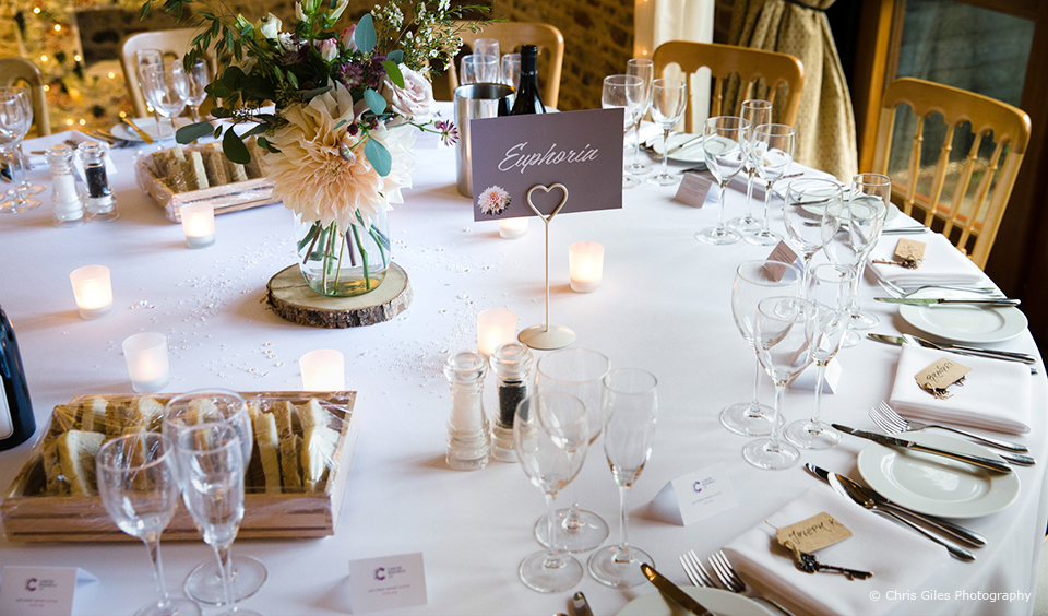 A table is set up for a wedding reception in the South Barn at Upwaltham Barns