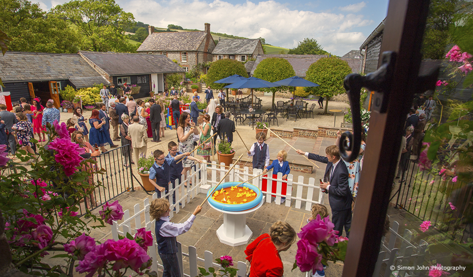 Children play hook-a-duck during a wedding reception in the Courtyard at Upwaltham Barns