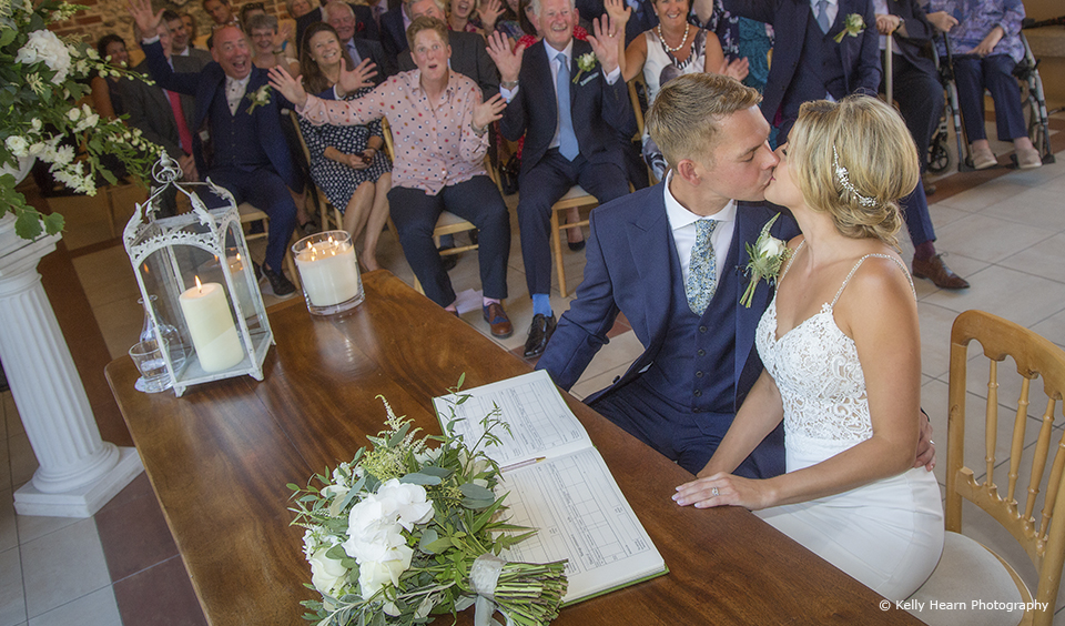 The bride and groom share a kiss after signing the wedding register at Upwaltham Barns