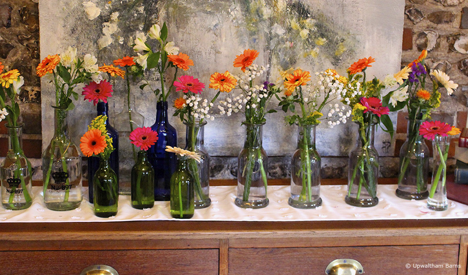 Bright florals sit in glass bottles for a vibrant summer wedding at Upwaltham Barns