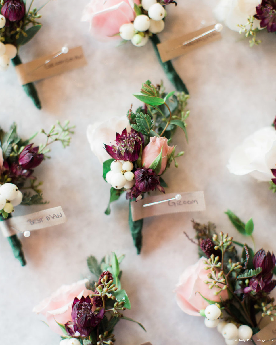 A couple chose burgundy florals as accents for their summer wedding at Upwaltham Barns