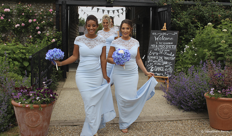 For a summer wedding at Upwaltham Barns bridesmaids wear dusty blue bridesmaid dresses