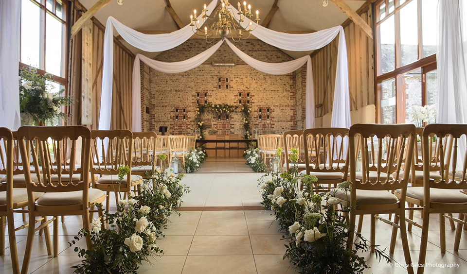 The East Barn at Upwaltham Barns is decorated with white and green florals and drapes