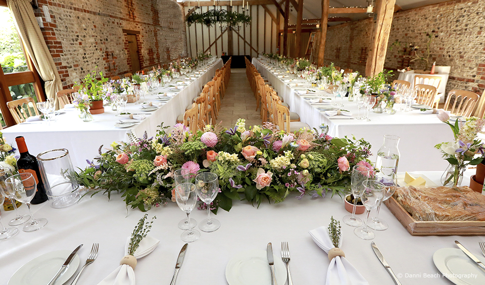 A pastel inspired floral garland dresses the top table in the South Barn at Upwaltham Barns for a summer wedding reception