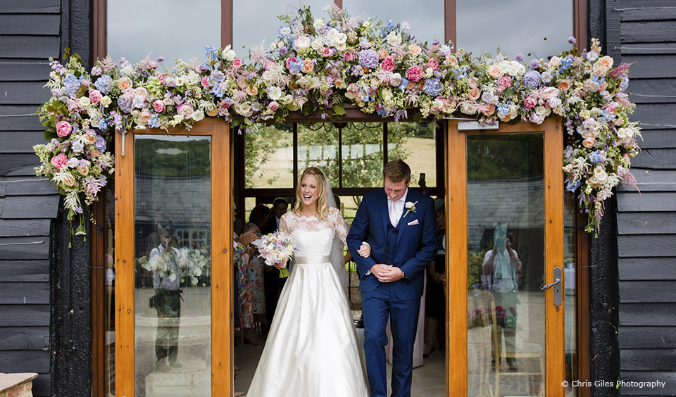 A large pastel flower garland hangs above the entrance to the East Barn at Upwaltham Barns
