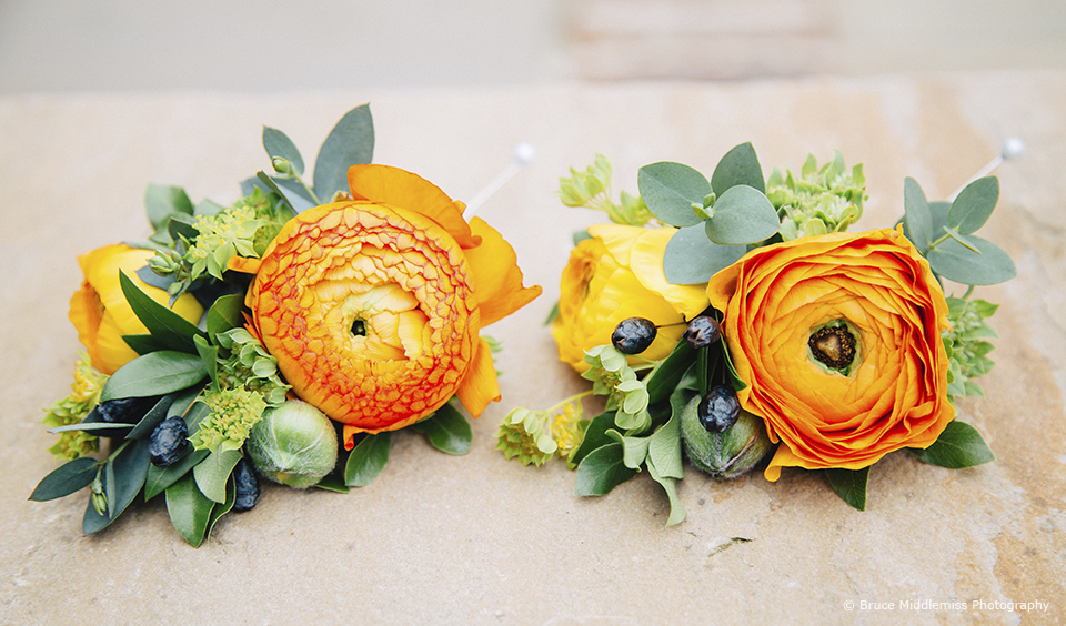 Orange floral buttonholes are perfect for a citrus wedding theme at Upwaltham Barns