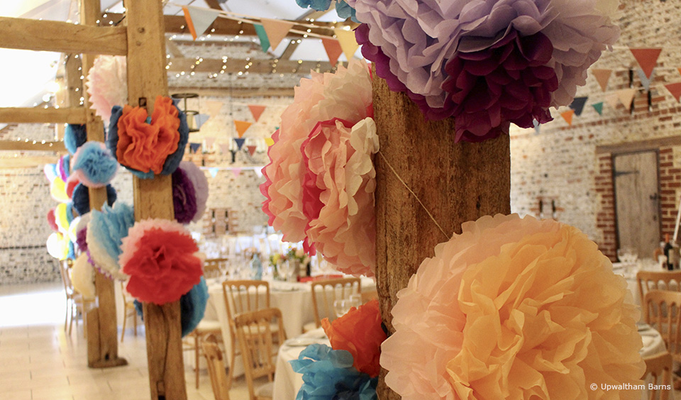 Bright coloured pom poms decorate the South Barn at Upwaltham Barns wedding venue in Sussex