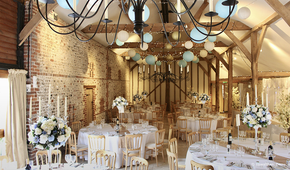 The South Barn at Upwaltham Barns is set up for a wedding reception with blue and white wedding flowers