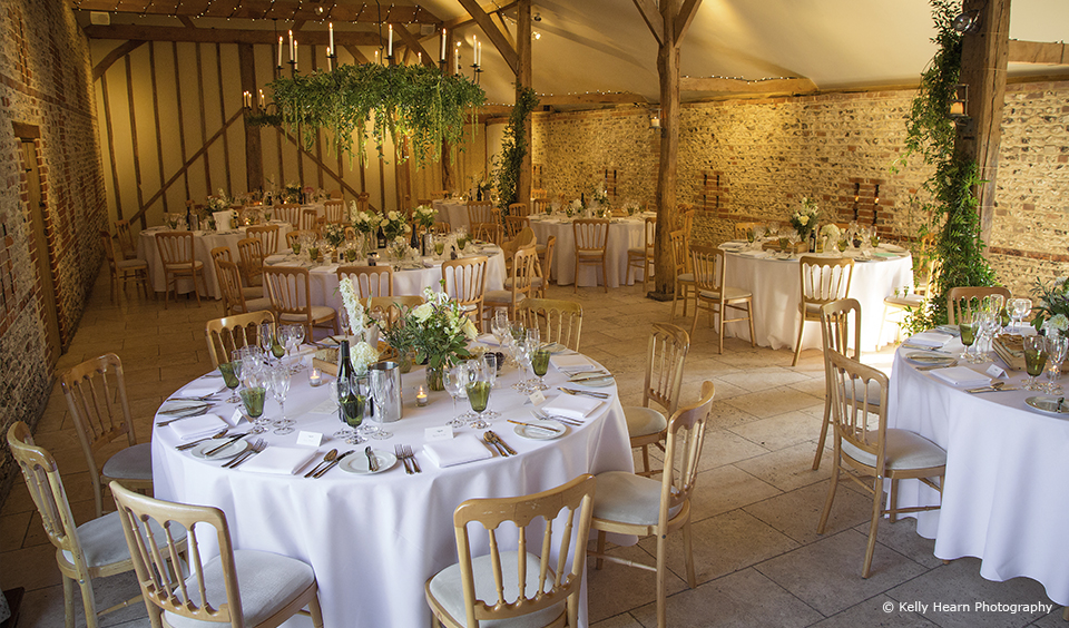 The South Barn at Upwaltham Barns is decorated with green foliage for an autumn wedding reception