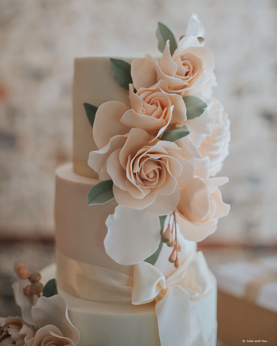 A traditional wedding cake at Upwaltham Barns is decorated with peach and sage icing flowers