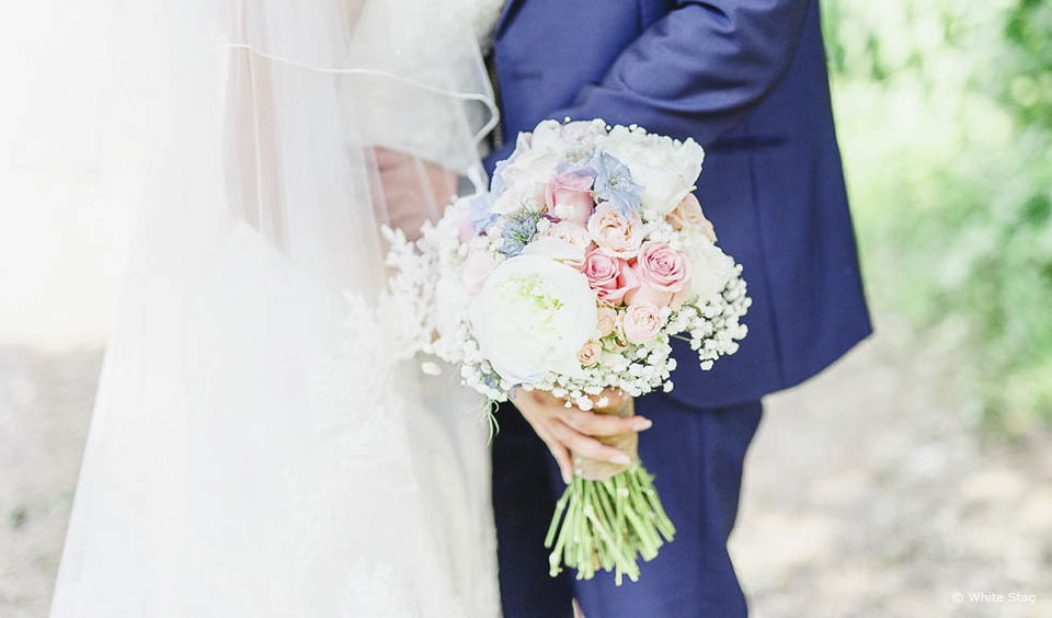A blue and peach wedding bouquet is the perfect colour choice for a summer wedding at Upwaltham Barns