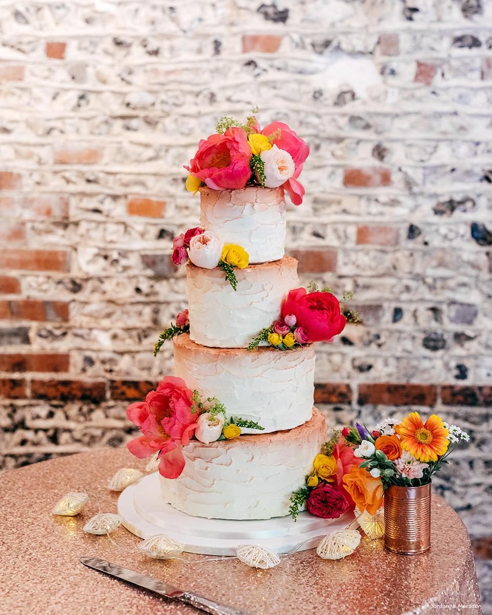 A wedding cake at Upwaltham Barns wedding venue is decorated with bright clashing florals