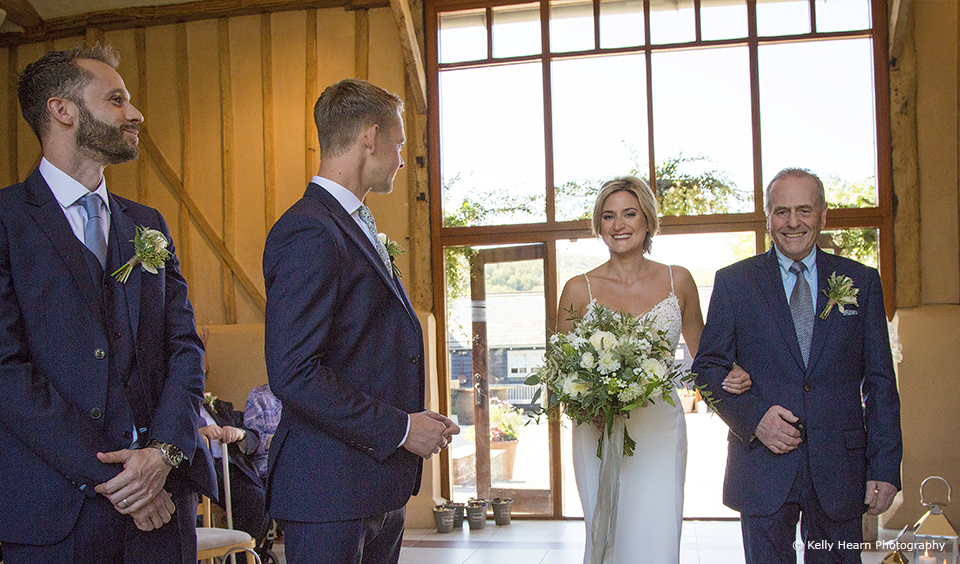 The bride and her father enter the South Barn at Upwaltham Barns for the wedding ceremony