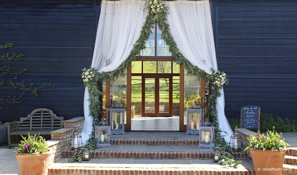 The doors to the East Barn at Upwaltham Barns are decorated with large white drapes and green foliage