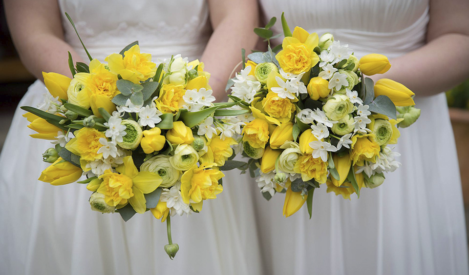 Brides hold bright yellow wedding bouquets for their summer weddign at Upwaltham Barns