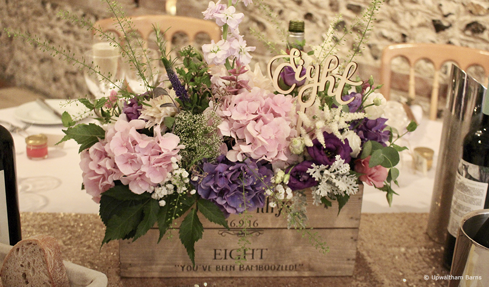 Fill a crate with wedding flowers to create a rustic wedding table centrepiece at Upwaltham Barns