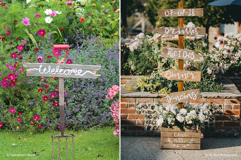 A handmade rustic wedding sign directs guests around Upwaltham Barns