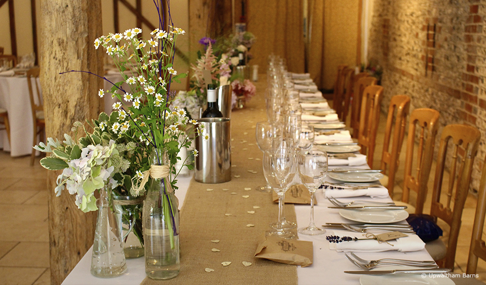 Add flowers to jars wrapped with twine to create rustic table decorations for your wedding breakfast at Upwaltham Barns