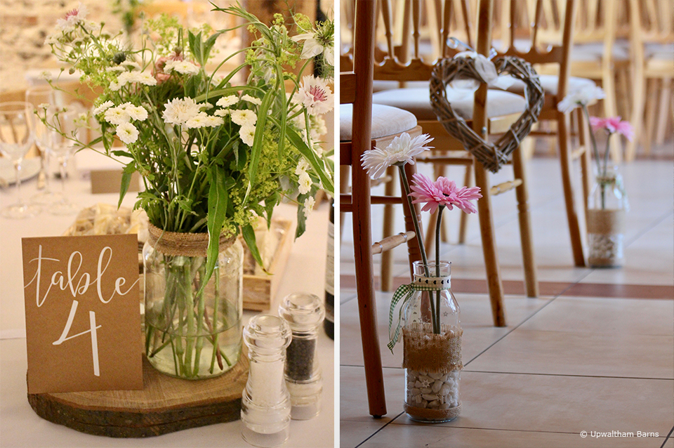 DIY jars filled with wedding flowers line the aisle in the East Barn at Upwaltham Barns