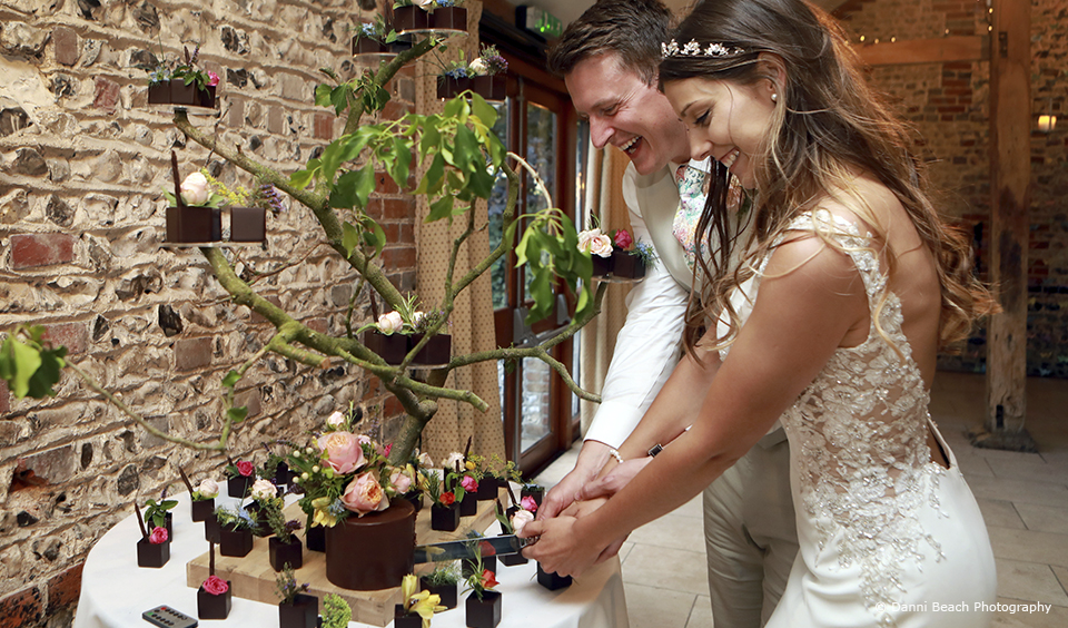 The newlyweds cut their wedding cake during their summer wedding reception at Upwaltham Barns