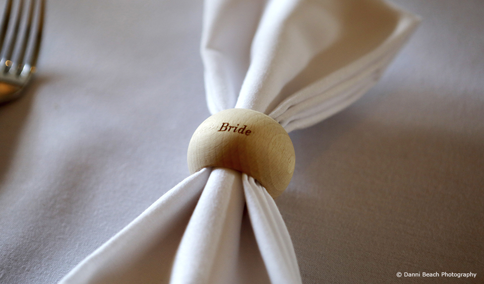 Personalised napkin holders created simple wedding favours and place names for this summer wedding at Upwaltham Barns