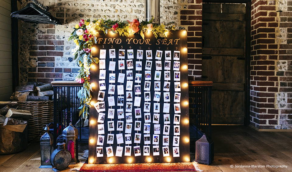 A table plan is personalised using pictures of wedding guests for a creative wedding at Upwaltham Barns