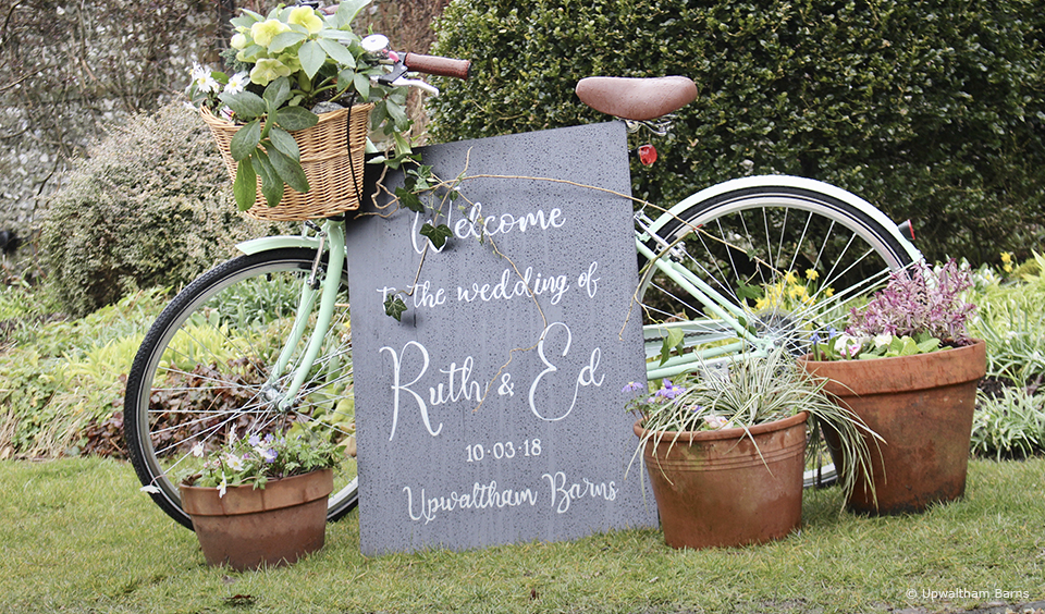 A rustic wedding sign is propped up by a vintage bike at Upwaltham Barns