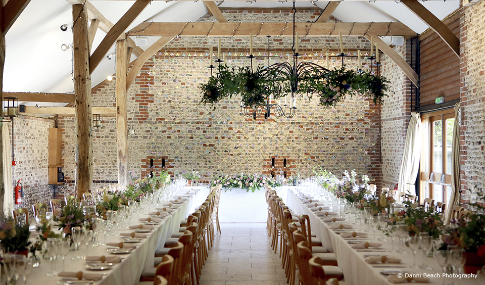 The South Barn at Upwaltham Barns is set up with long banquet style tables for a summer wedding reception