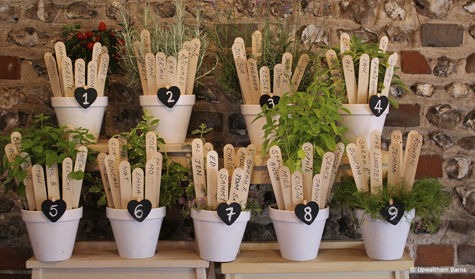 Plant pots are used as an alternative rustic wedding table plan for a wedding at Upwaltham Barns