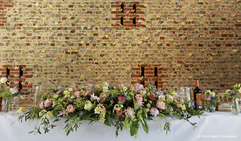 The top table in the South Barn at Upwaltham Barns is decorated with a large floral display