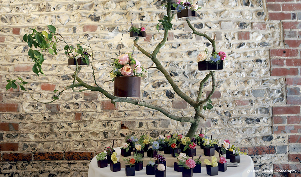 Wedding cakes sit on tree branches as an alternative wedding cake stand in the South Barn at Upwaltham Barns