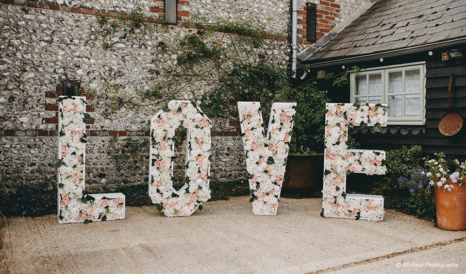 Floral giant love letters are displayed in the courtyard at Upwaltham Barns