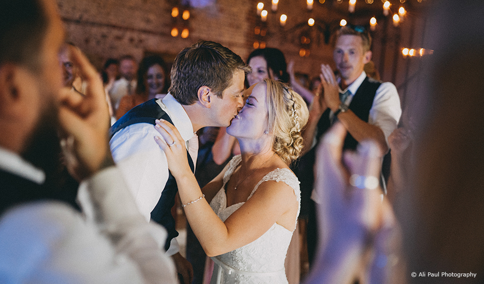 The newlyweds perform their first dance in front of guests in the South Barn at Upwaltham Barns