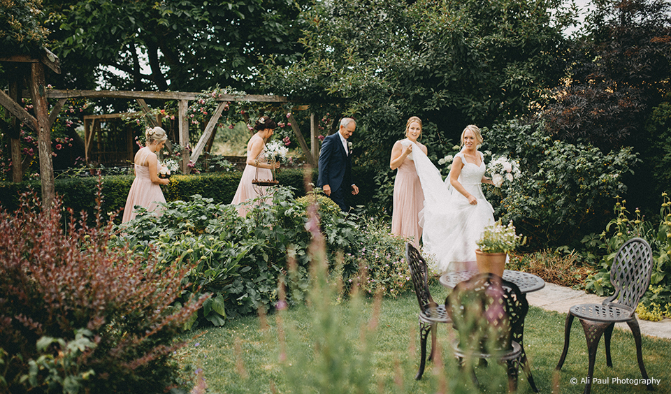 Three bridesmaids wear blush pink bridesmaid dresses for a summer wedding at Upwaltham Barns