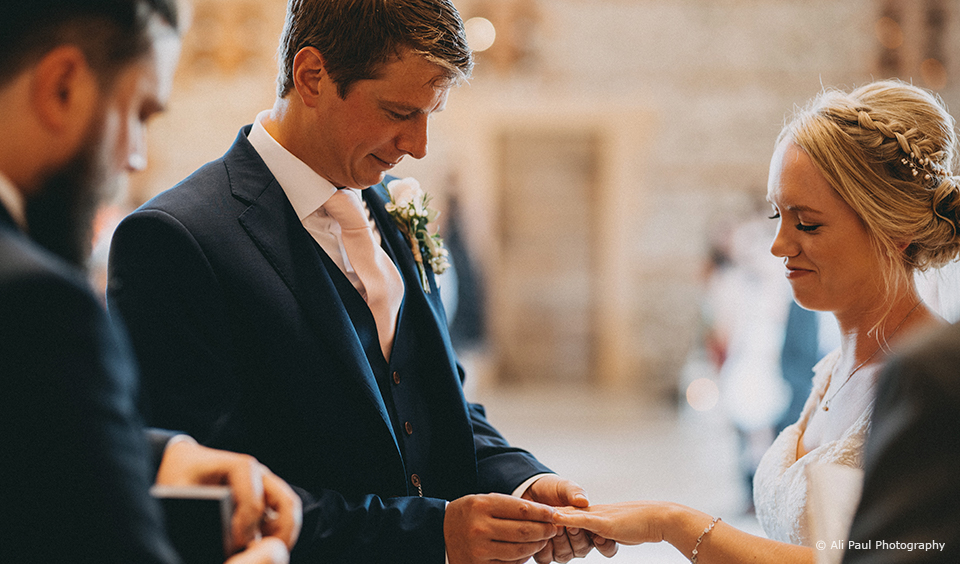 The bride and groom exchange wedding rings during their summer wedding ceremony at Upwaltham Barns