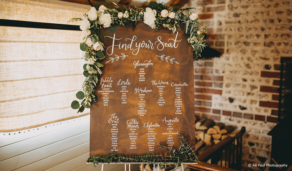 A wooden wedding table plan is decorated with white and green florals for a summer wedding at Upwaltham Barns