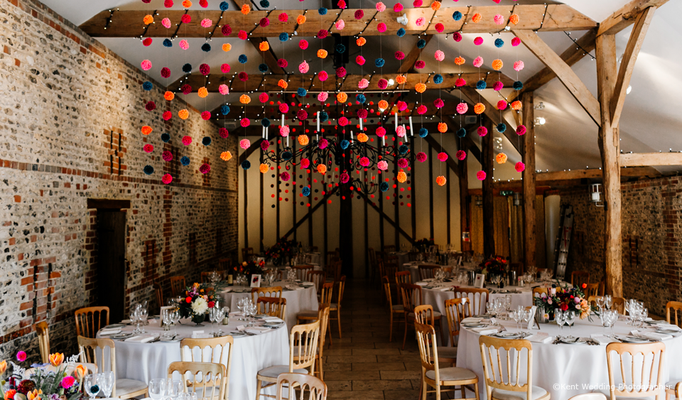 A couple created their own DIY wedding decorations in the South Barn at Upwaltham Barns