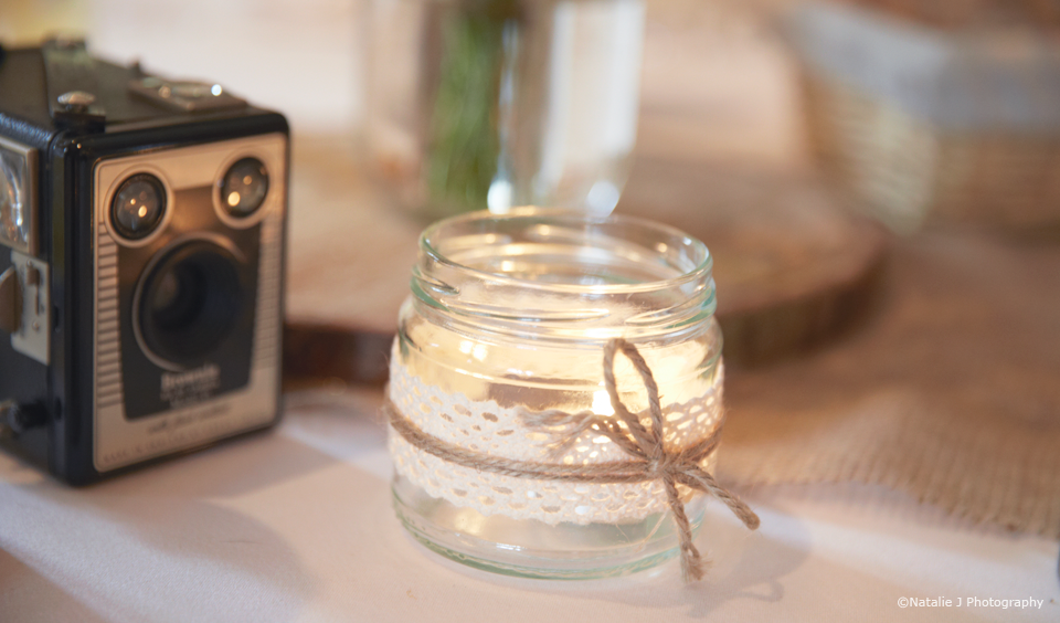A jam jar is wrapped in lace for a DIY wedding decoration at Upwaltham Barns