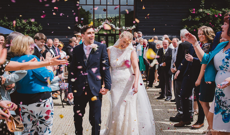 Newlyweds are showered in wedding confetti after their wedding ceremony at Upwaltham Barns